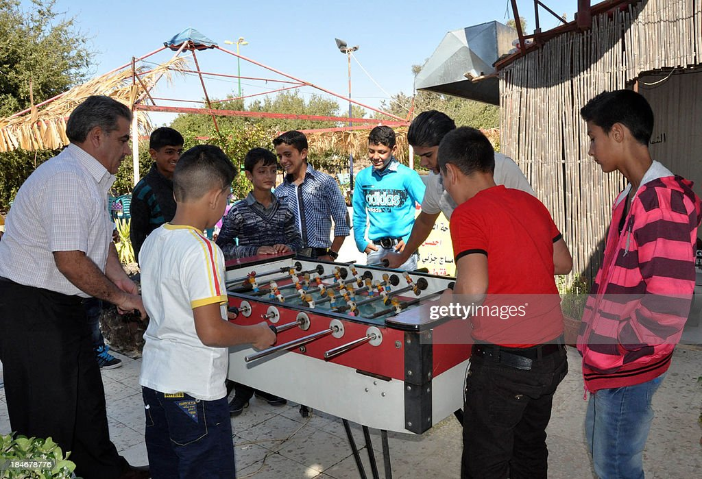Syrian boy play table football as families celebrate the Muslim feast of Eid al-Adha, or 'Feast of the Sacrifice' at a fun fair in Suweida, south of the capital Damascus, on October 15, 2013. Eid al-Adha, which commemorates the willingness of Abraham (Ibrahim in Arabic) to sacrifice his son at God's command, is the biggest Muslim holiday of the year.