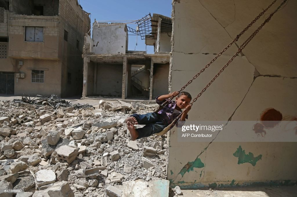 Syrian boy plays on a swing in a destroyed building in the rebel-held town of Douma, on the eastern outskirts of Damascus, as Muslims celebrate the third day of the Eid al-Adha holiday on September 3, 2017. /