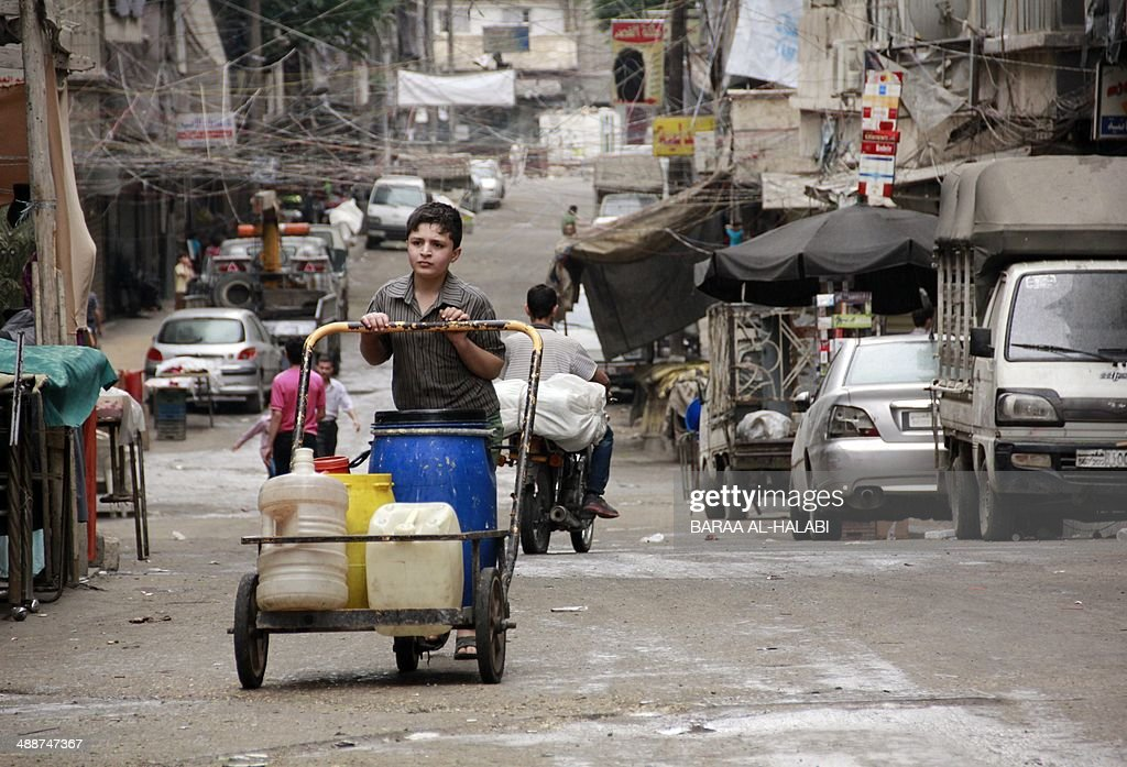 A Syrian boy pushes a cart with jerrycans filled with water in Aleppo on May 8, 2014 as residents of the northern city suffer constant water shortages due to the three-year-long conflict. Syria's uprising began with peaceful protests in March 2011 but escalated into an insurgency after the regime opened fire on demonstrators. An estimated 150,000 people have been killed since the revolt began.