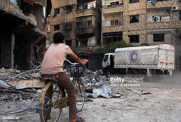 Syrian boy rides his bike behind a Syrian Arab Red Crescent truck delivering aid in the rebelheld area of Harasta on the northeastern outskirts of...