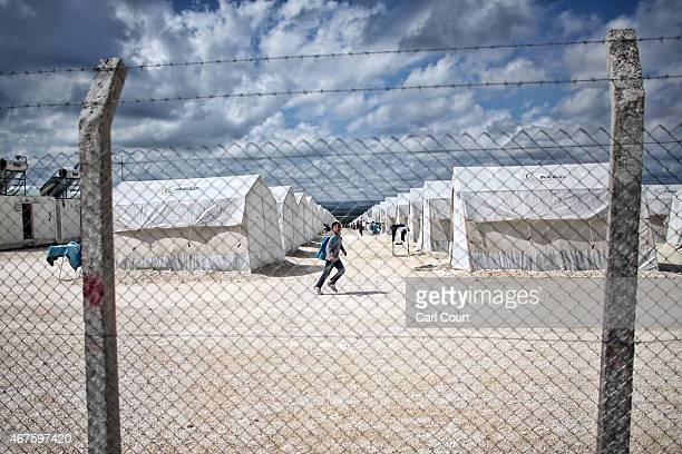 Syrian boy runs alongside tents in Suruc refugee camp on March 25 2015 in Suruc Turkey The camp is the largest of its kind in Turkey with a...