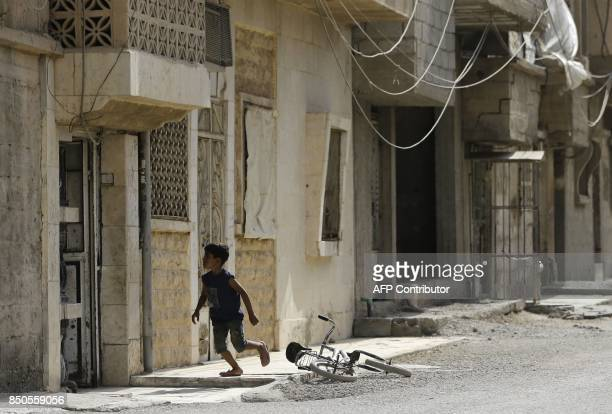 Syrian boy runs near his bicycle in the eastern Syrian city of Deir Ezzor on September 21 2017 as Syrian government forces continue to press forward...