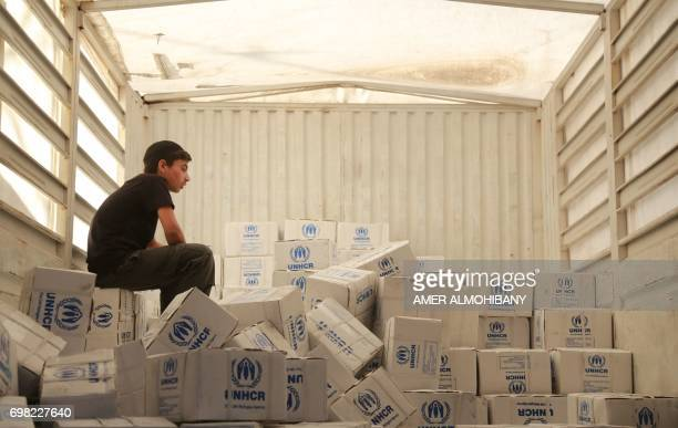 A Syrian boy sits amidst boxes of aid donated by the UNHCR in the rebel held and besieged town of Harasta in the Eastern Ghouta region outside...
