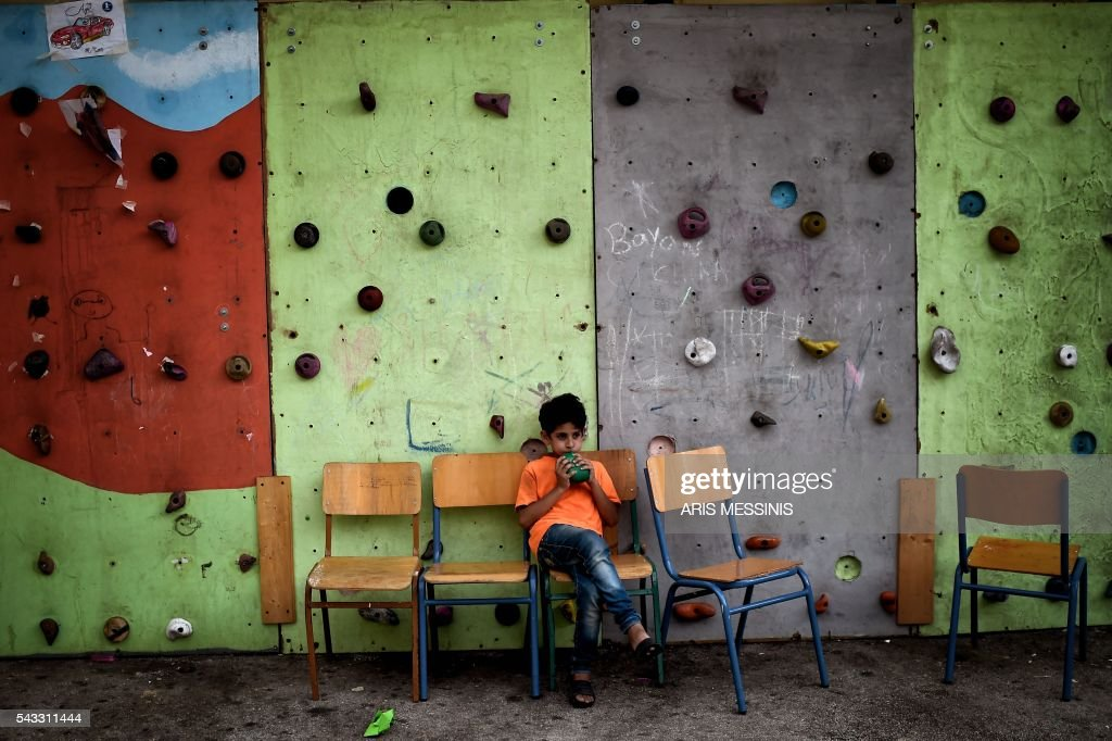 A Syrian boy sits at the yard of an abandoned school used by volunteers for hosting families of refugeees from Syria and Afghanistan in Athens on June 27, 2016. / AFP / ARIS