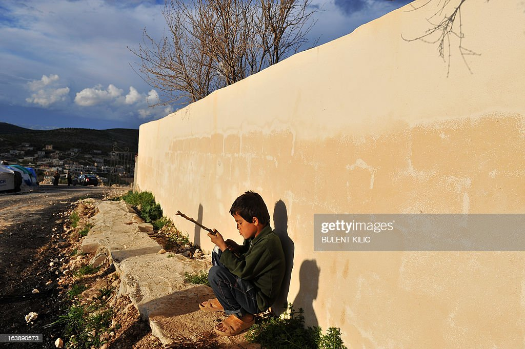 A Syrian boy sits next to a wall outside his makeshift house at the refugee camp of Qah along the Turkish border in the village of Atme in the northwestern province of Idlib, on March 17, 2013. The conflict has killed at least 70,000 people, and forced more than one million Syrians to seek refuge abroad. Millions more have been internally displaced.