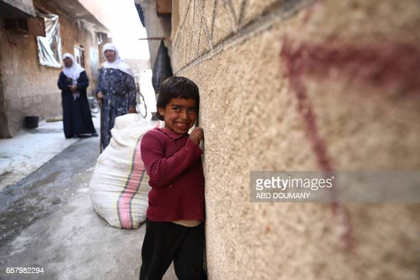 A Syrian boy smiles to the camera in the rebelcontrolled town of Kafr Batna in the eastern Ghouta region on the outskirts of the capital Damascus on...
