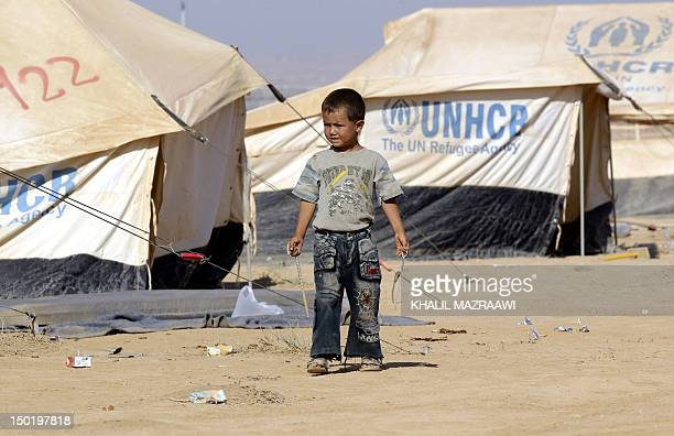 Syrian boy stands next to a UNHCR tent at the Zaatari camp for Syrian refugees outside the northern Jordanian city of Mafraq on August 12 as French...