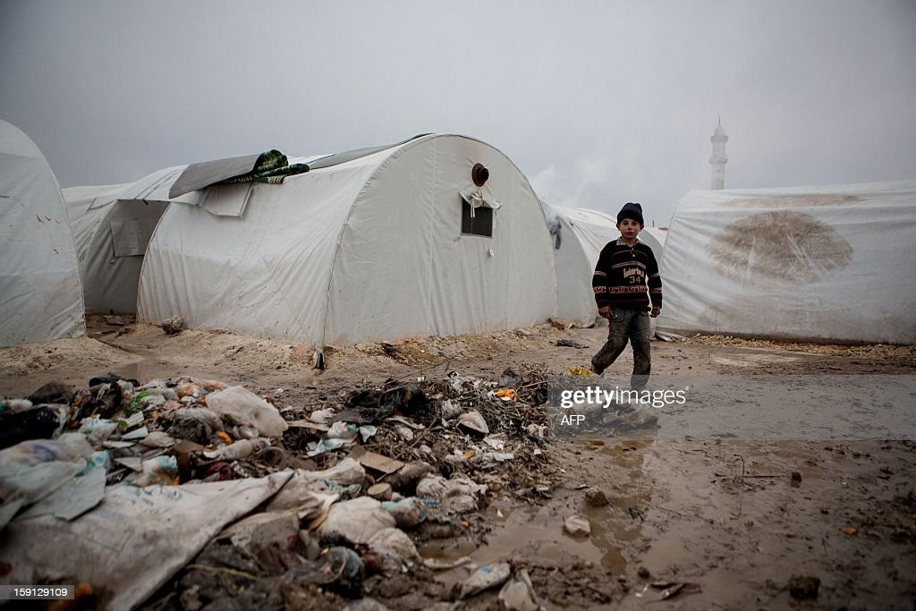A Syrian boy walks near rubbish next to tents at a refugee camp near the northern city of Azaz on the Syria-Turkey border, home to more than 7000 people mostly from the northern districts of Aleppo and Marea, on January 8, 2013. The internally displaced faced further misery due to increasing shortage of supplies as heavy rain was followed by a drop in temperatures.