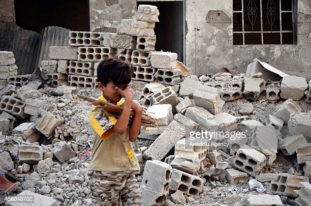 Syrian boy walks next the rubble of a collapsed building following the Syrian army's airstrikes on the opposition controlled Duma district in the...