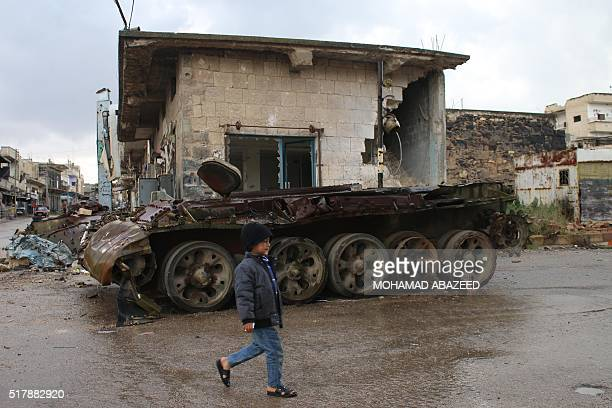 A Syrian boy walks past the wreckage of a tank in a rebelheld area of Daraa in southern Syria on March 28 2016 / AFP / MOHAMAD ABAZEED