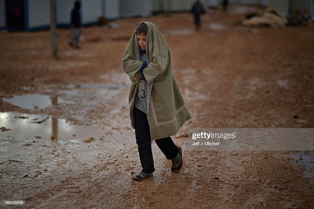 ZA'ATARI, JORDAN - JANUARY 31: A Syrian boy walks through mud following overnight rain in the Za'atari refugee camp on January 31, 2013 in Za'atari, Jordan. Record numbers of refugees are fleeing the violence and bombings in Syria to cross the borders to safety in northern Jordan and overwhelming the Za'atari camp. The Jordanian government are appealing for help with the influx of refugees as they struggle to cope with the sheer numbers arriving in the country.