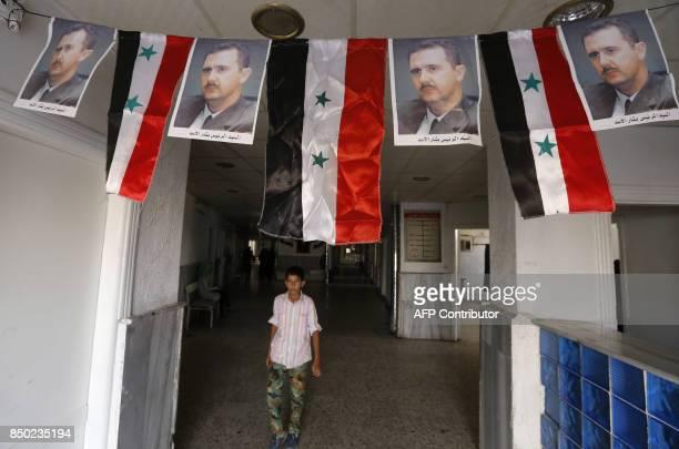 A Syrian boy walks under portraits of Syrian President Bashar alAssad adorning a hospital in the eastern city of Deir Ezzor on September 20 2017 as...