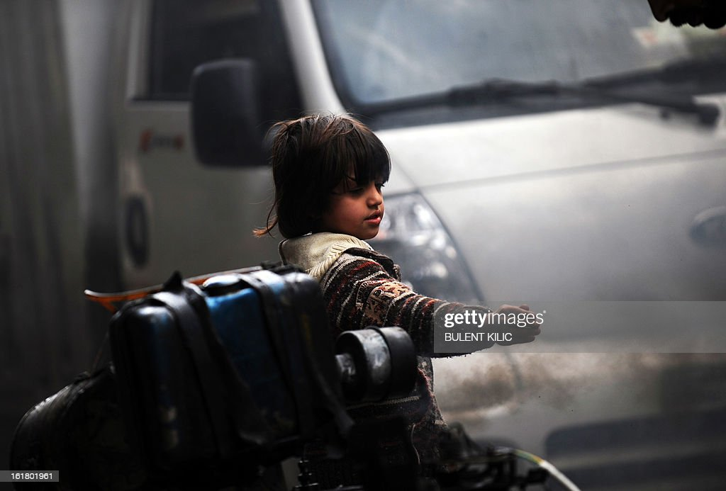 A Syrian boy warms his hand with generator smoke in the Salaheddine neighbourhood of Aleppo on February 16, 2013. More than 300 people were abducted by armed groups in northwestern Syria over two days in an unprecedented string of sectarian kidnappings, a watchdog and residents said. AFP PHOTO/BULENT KILIC