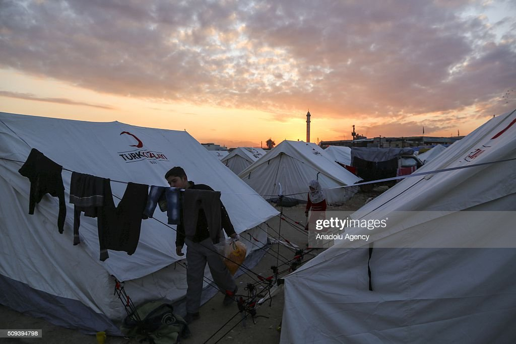 A Syrian boy, who fled bombing in Aleppo, carries bags with food in them at a tent city close to the Bab al-Salam border crossing on Turkish-Syrian border near Azaz town of Aleppo, Syria on February 10, 2016. Russian airstrikes have recently forced some 40,000 people to flee their homes in Syrias northern city of Aleppo.