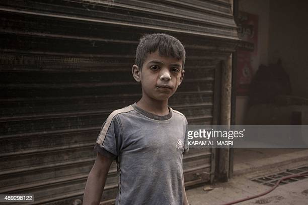 A Syrian boy with his face covered in dust and traces of his tears stands in a street following an air strike by government forces on the rebel held...