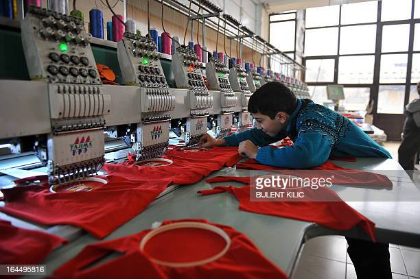 Syrian boy works at a clothes factory in the northern city of Aleppo on March 23 2013 In a building in the eastern district of Tariq alBab the din of...