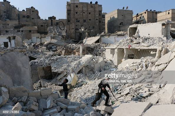 Syrian boys play in the ruins of a destroyed building in the northern Syrian city of Aleppo on November 18 2014 Aleppo has been divided between...
