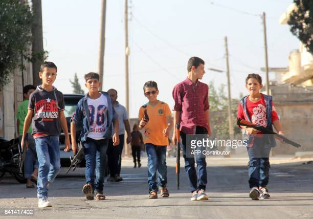 Syrian boys play with toy plastic guns and rifles on the morning of the first day of Eid alAdha or the Festival of Sacrifice in the rebelheld town of...