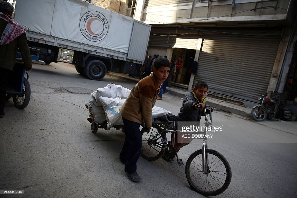 Syrian boys pull a cart in front of a lorry of the Syrian Arab Red Crescent containing aid parcels upon its arrival on February 13, 2016 in the rebel-held city of Douma, northeast of the capital Damascus. A Syrian Arab Red Crescent medical aid convoy made its way into Douma city, bringing milk for the children and medecines. / AFP / Abd Doumany