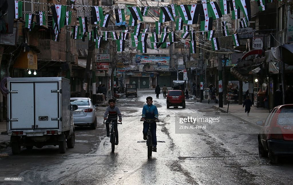 Syrian boys ride their bikes under preBaath Syrian flags that was adopted by the Syrian revolution during the uprising in the northern Syrian city of...