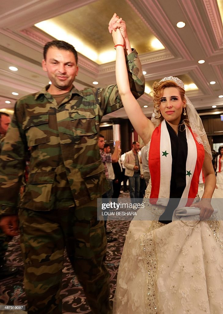 A Syrian bride, draped in a scarf bearing the colours of her national flag dances with her groom following a group wedding ceremony consisting of twenty couples made up of government soldiers and their brides in Damascus on April 29, 2014.
