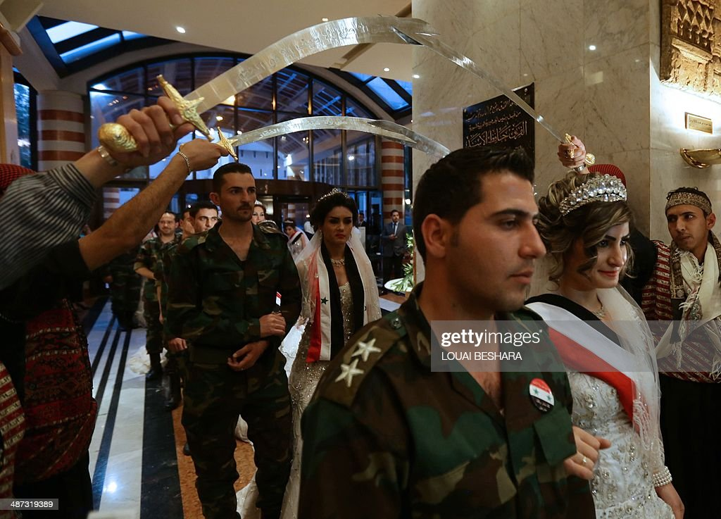 Syrian brides and grooms arrive for a reception following a group wedding ceremony consisting of twenty couples made up of government soldiers and their brides in Damascus on April 29, 2014. AFP PHOTO/LOUAI BESHARA