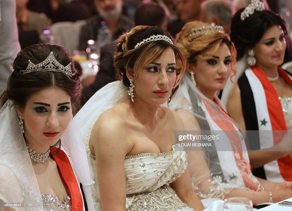 Syrian brides of government soldiers, draped in scarves bearing the colours of their national flag, sit at a table during a meal following a group wedding ceremony in Damascus on April 29, 2014.