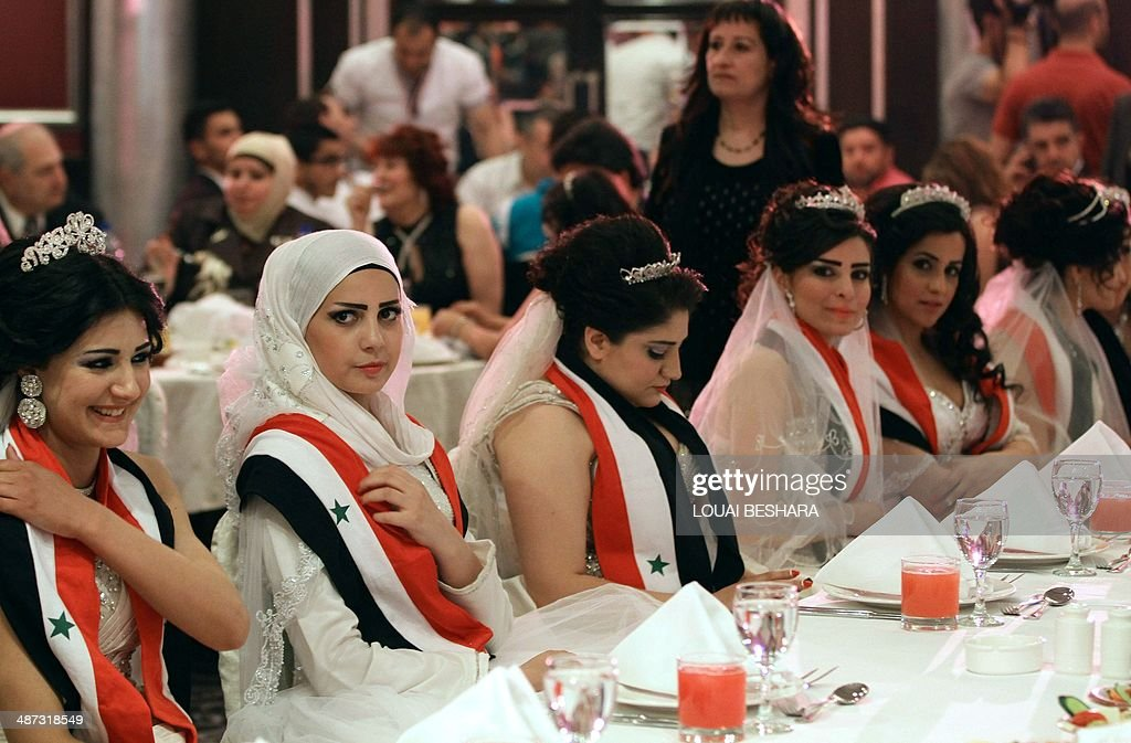 Syrian brides of government soldiers, draped in scarves bearing the colours of their national flag, sit at a table during a dinner following a group wedding ceremony in Damascus on April 29, 2014.