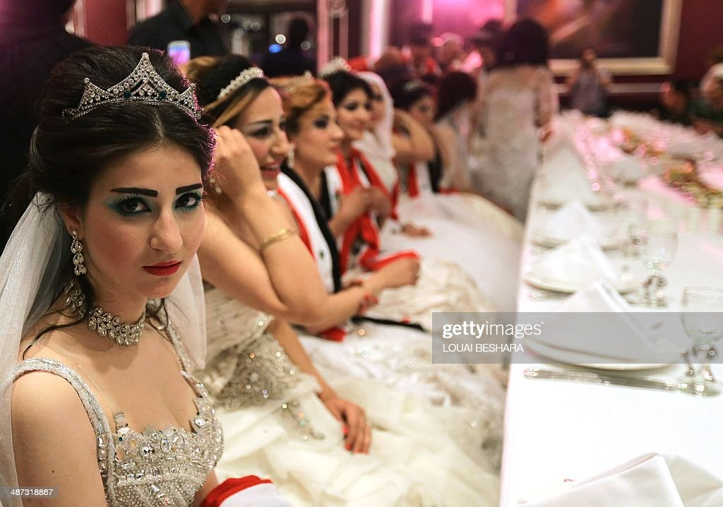 Syrian brides of government soldiers sit at a table during a meal following a group wedding ceremony consisting of twenty couples in Damascus on April 29, 2014.