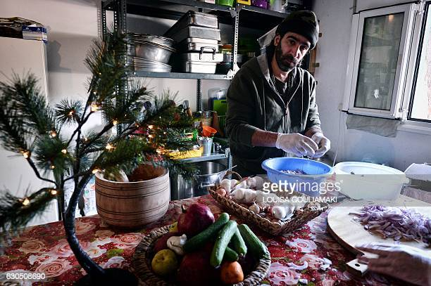 Syrian Chef Talal Rankoussi looks on as he prepares a meal for the volunteers working in the Ritsona camp some 80 km north of Athens on December 21...
