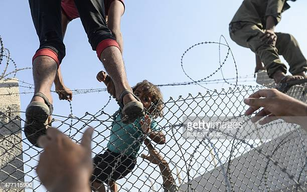 A Syrian child fleeing the war is lifted over border fences to enter Turkish territory illegally near the Turkish border crossing at Akcakale in...