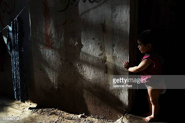 Syrian child from the city of Dara'a pauses in the doorway of her home she shares with extended members of her family in a poor neighborhood with a...