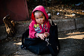 A Syrian child injured from a chemical attack according to her father waits to reach a train heading to the border with Serbia at the train station...