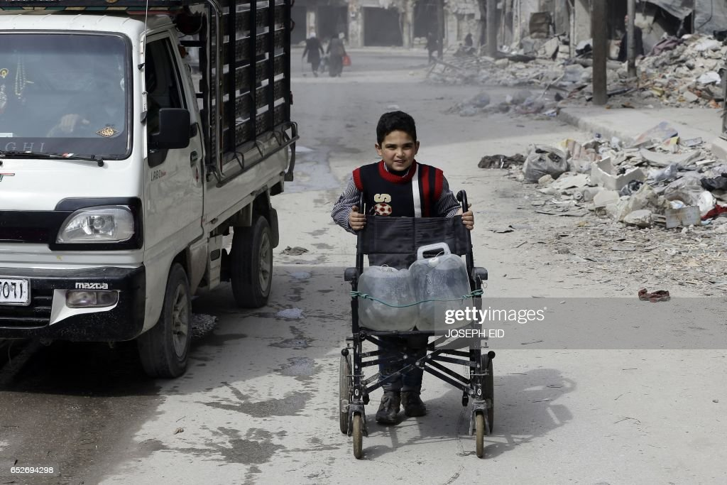 Syrian child pushes a wheelchair carrying water bottle in the once rebel-held Shaar neighbourhood in the Northern Syrian city of Aleppo on March 9, 2017. /