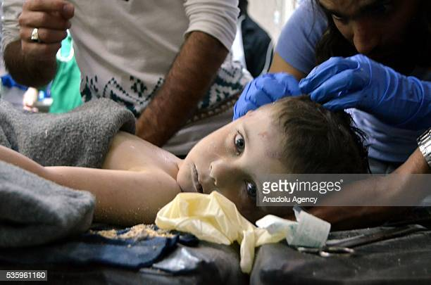 Syrian child receives treatment at a hospital after the Russian airstrikes targeted the National Hospital in Idlib Syria on May 31 2016