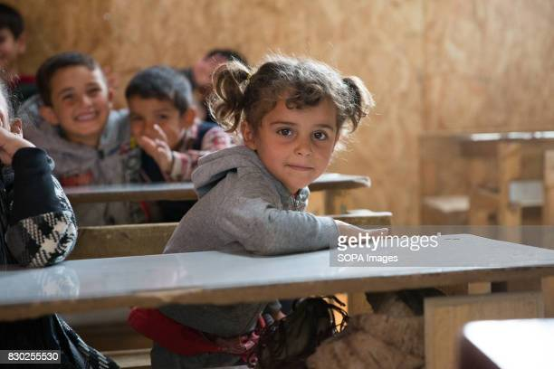 Syrian Child refugee smiles as she is pictured at a school in a refugee settlement close to the Syrian border