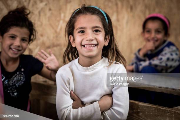 Syrian child refugee smiles as she poses for a picture during a classroom inside the newly built Al Marj refugee settlement school