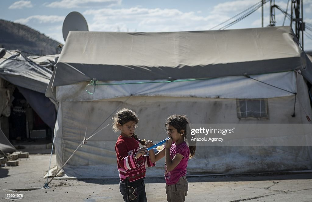 Syrian child refugees playing flute among the tents at a refugee camp site which is constructed by Turkish Prime Ministry's Disaster and Emergency...