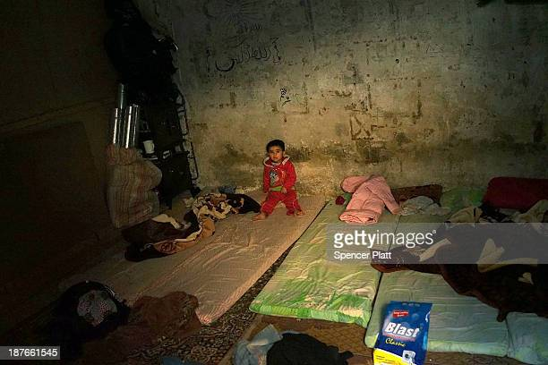 Syrian child sits alone in a room in a former prison now being occupied by Syrian refugees in the Bekaa Valley close to the border with Syria on...