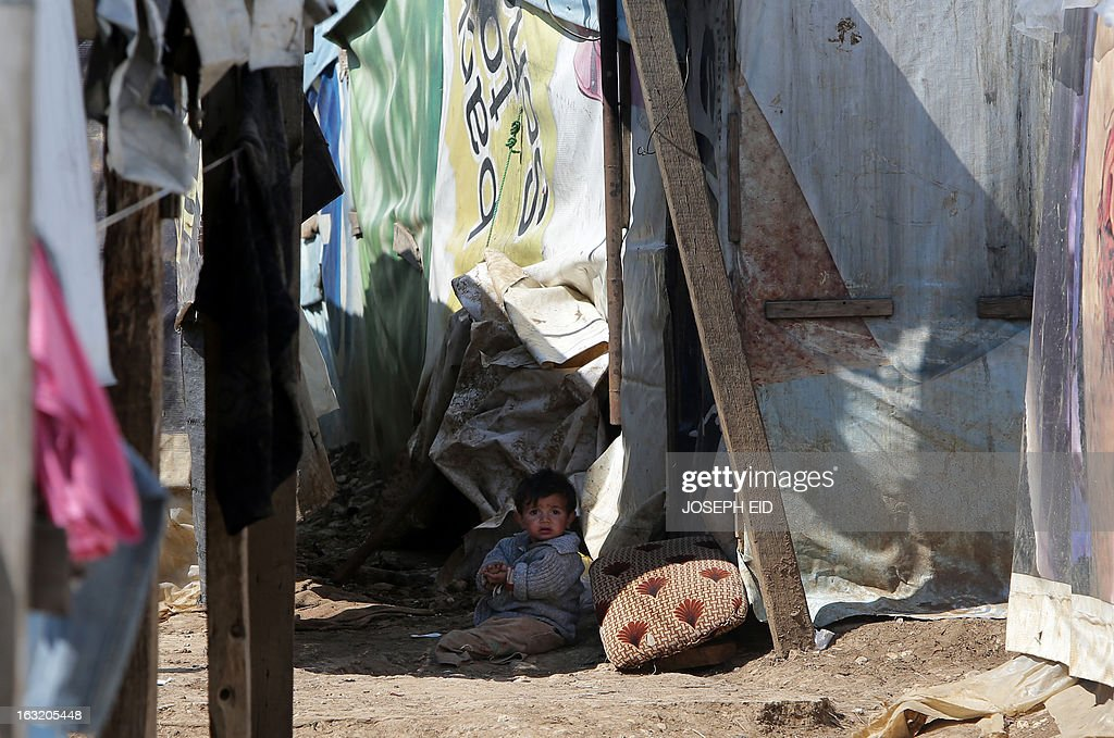 "A Syrian child sits in the mud at the entrance of his makeshift house at a refugee camp in the village of Saadnayel in the Bekaa valley on March 6, 2013. The number of Syrians who have fled their war-ravaged country and are seeking assistance has now topped the 1 million mark, the UN refugee agency said, warning that Syria is heading towards a ""full-scale disaster."""