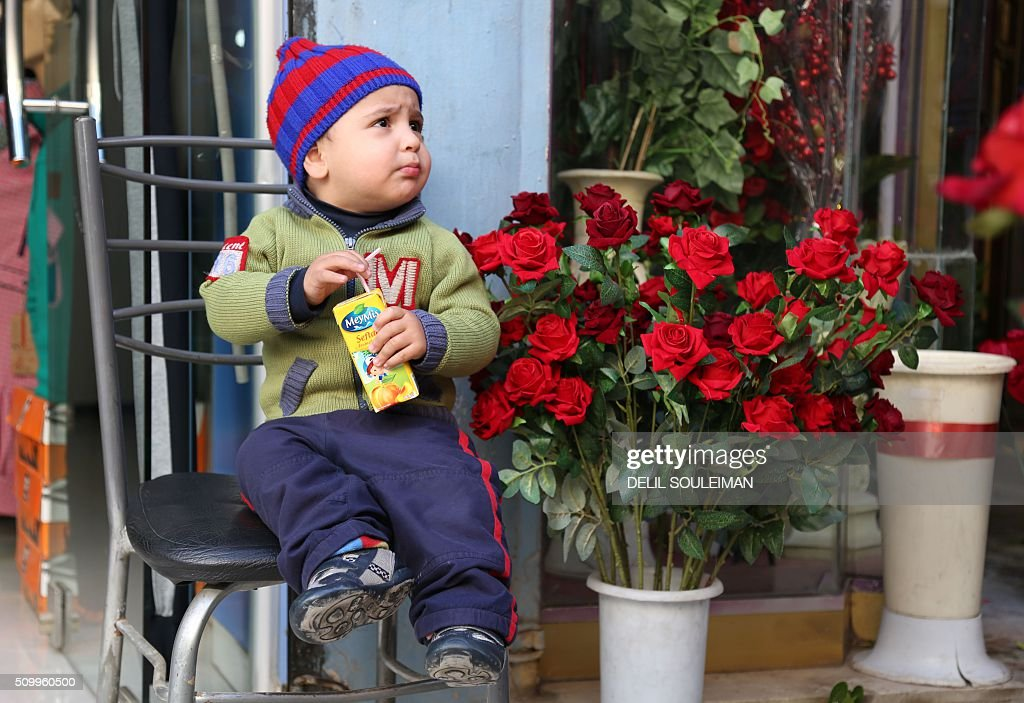 A Syrian child sits outside a shop displaying Valentine's day gifts in the northeastern city of Qamishli, on February 13, 2016. / AFP / DELIL SOULEIMAN