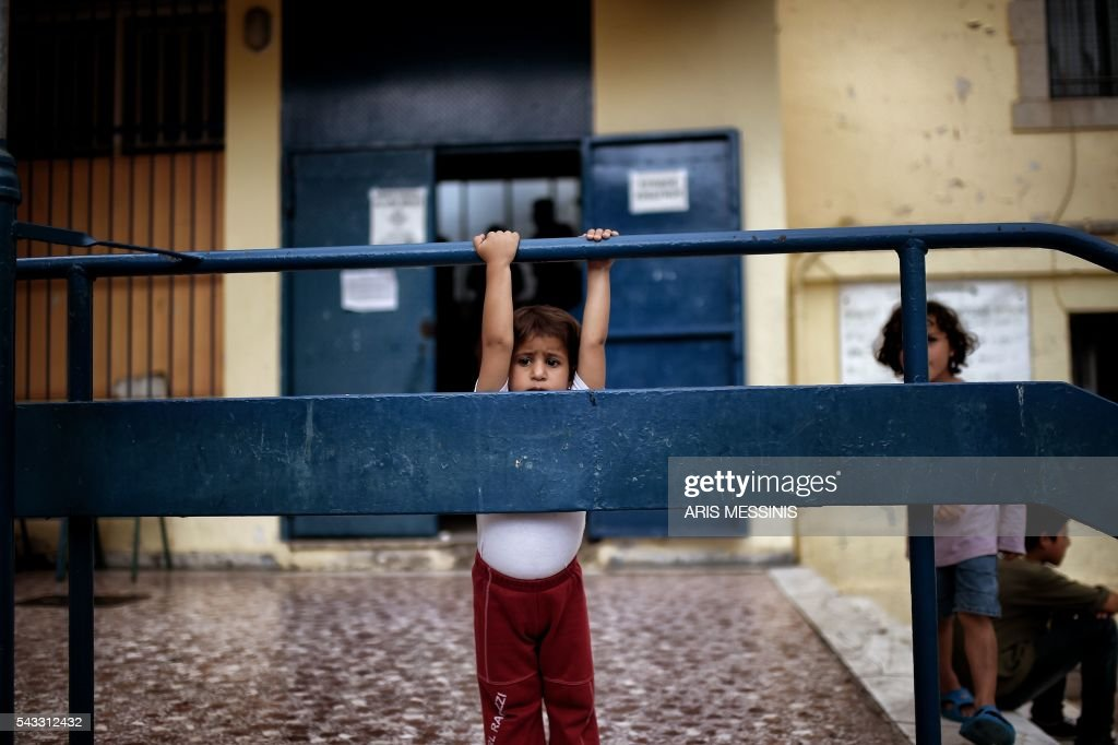 A Syrian child stands at the yard of an abandoned school used by volunteers for hosting families of refugeees from Syria and Afghanistan in Athens on June 27, 2016. / AFP / ARIS