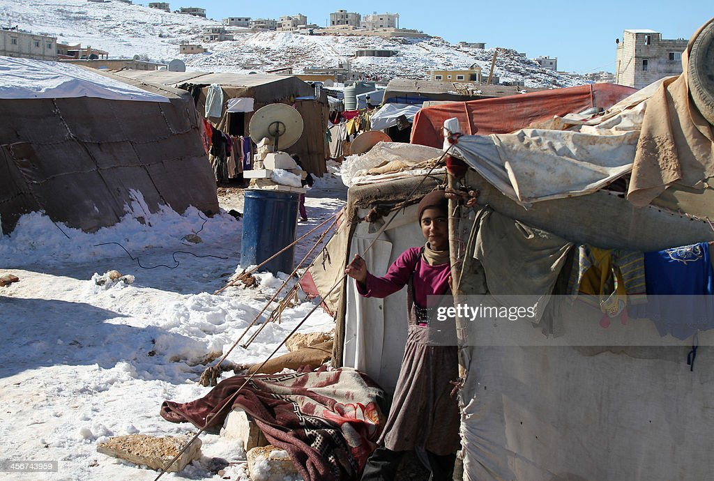 A Syrian child stands behind a tent in a refugee camp on December 15, 2013, in the town of Arsal in the Lebanese Bekaa valley. Thousands of Syrian refugees living in makeshift camps in Lebanon were weathered a winter storm that brought snow, rain and freezing temperatures to the country.