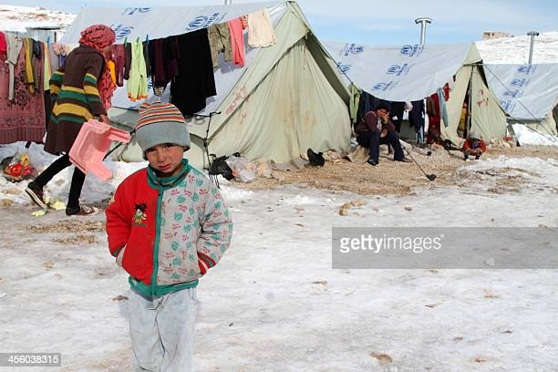 A Syrian child stands in the snow in a refugee camp in the town of Arsal in the Lebanese Bekaa valley on December 13 2013 Thousands of Syrian...