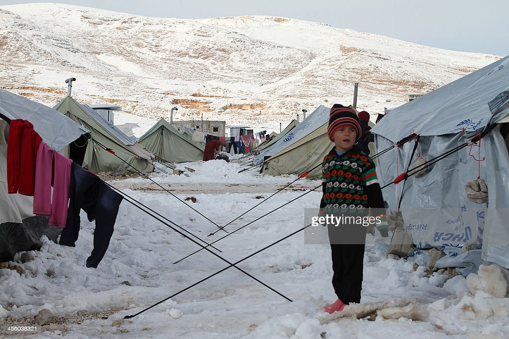 A Syrian child stands in the snow in a refugee camp in the town of Arsal in the Lebanese Bekaa valley on December 13, 2013. Thousands of Syrian refugees living in makeshift camps in Lebanon were weathered a winter storm that brought snow, rain and freezing temperatures to the country.