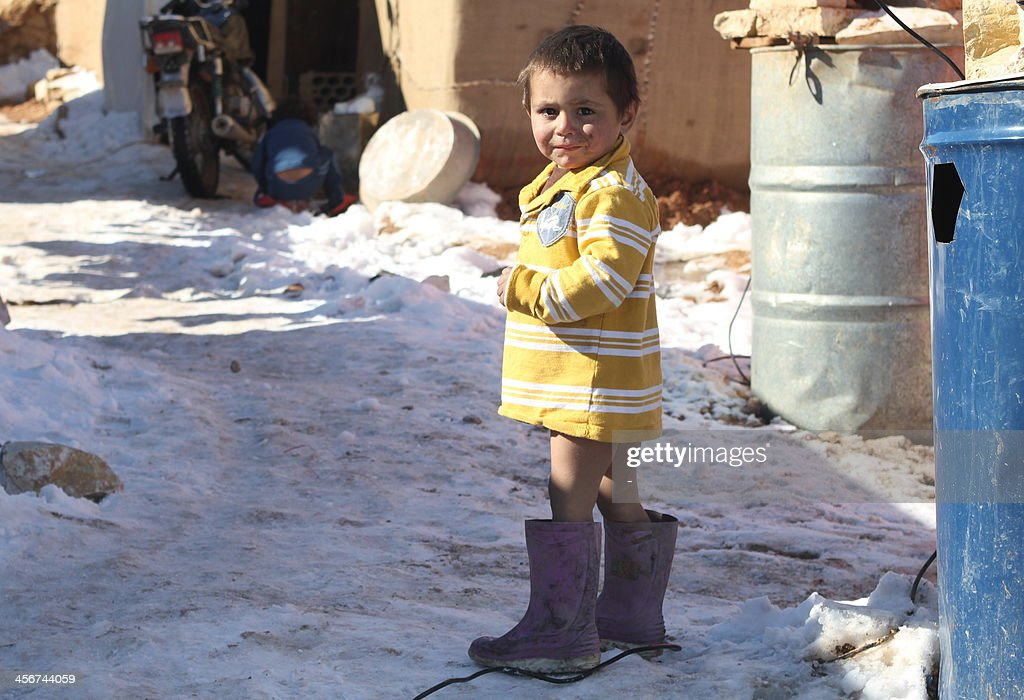 A Syrian child stands in the snow in the Arsal refugee camp in the Lebanese Bekaa valley on December 15, 2013. Thousands of Syrian refugees living in makeshift camps in Lebanon were weathered a winter storm that brought snow, rain and freezing temperatures to the country.