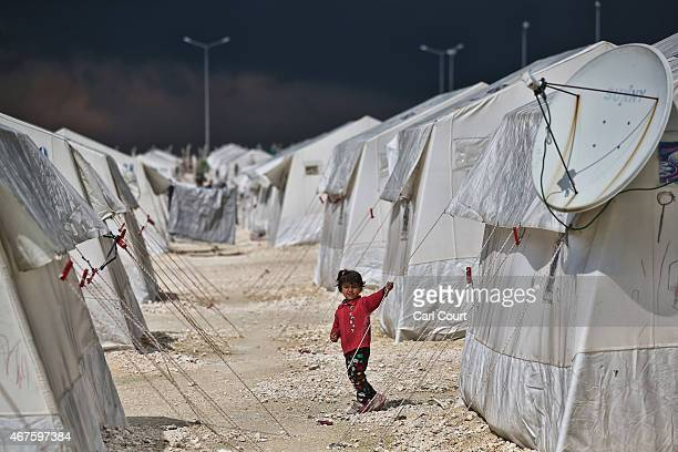 Syrian child walks between tents in Suruc refugee camp on March 25 2015 in Suruc Turkey The camp is the largest of its kind in Turkey with a...