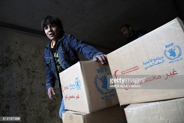 A Syrian child walks past boxes of aid provided by the World Food Programme in Kafr Batna in the rebelheld Eastern Ghouta area on the outskirts of...