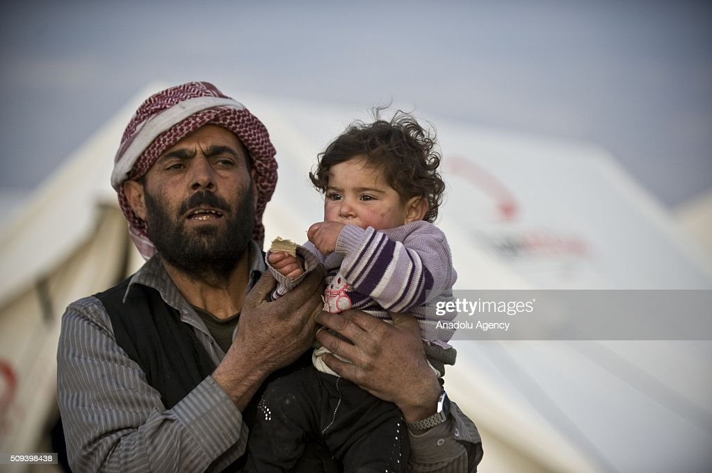A Syrian child, who fled bombing in Aleppo, is seen on her fathers arms at a tent city close to the Bab al-Salam border crossing on Turkish-Syrian border near Azaz town of Aleppo, Syria on February 10, 2016. Russian airstrikes have recently forced some 40,000 people to flee their homes in Syrias northern city of Aleppo.