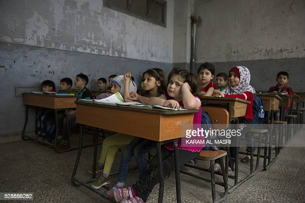 Syrian children attend a class at a primary school in Aleppo's rebelheld eastern district of Shaar on May 7 2016 Displaced families returned home and...